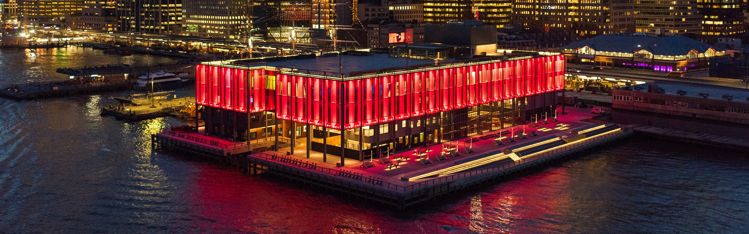 Pier 17 lit up in red lights